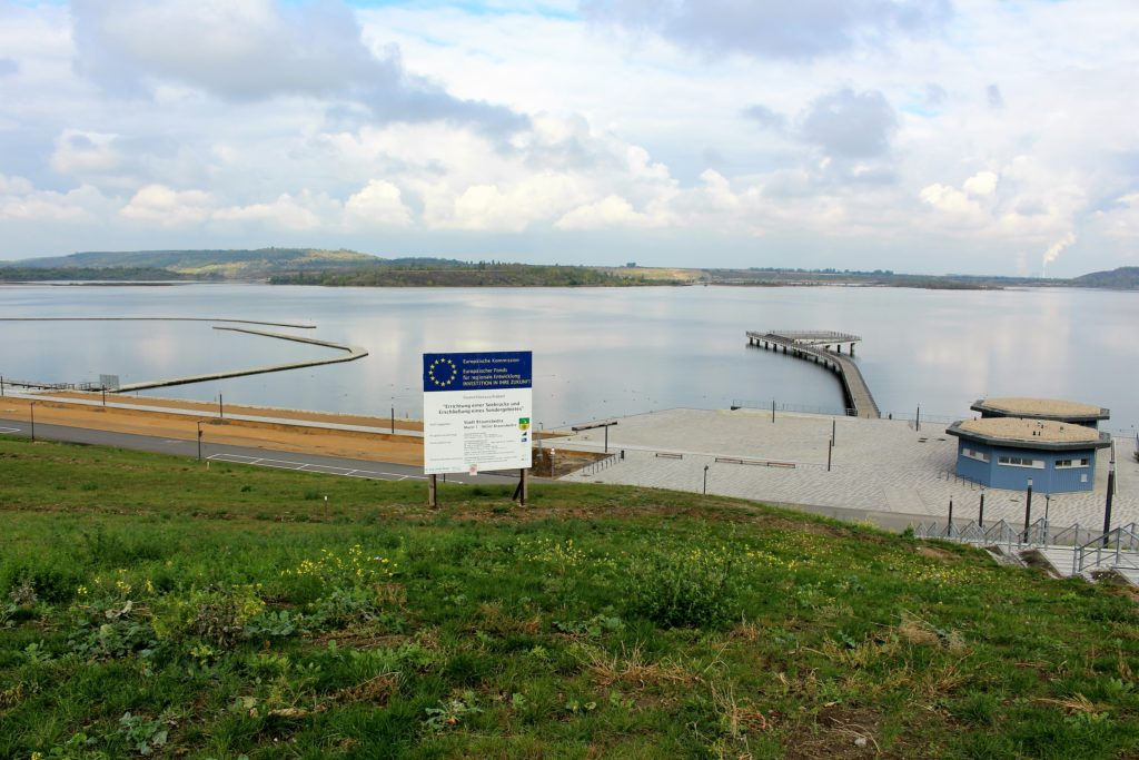 Geiseltalsee inSachsen-Anhalt: Im Vordergrund die Landungsbrücke mit einer Mole und dem Hinweisschild zur EU-Förderung.