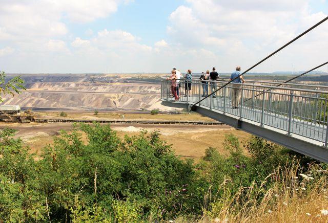 Der Skywalk, eine Konstruktion aus hellem Metall streckt sich über die Abbruchkante. Mehrere Menschen betrachten den Tagebau.