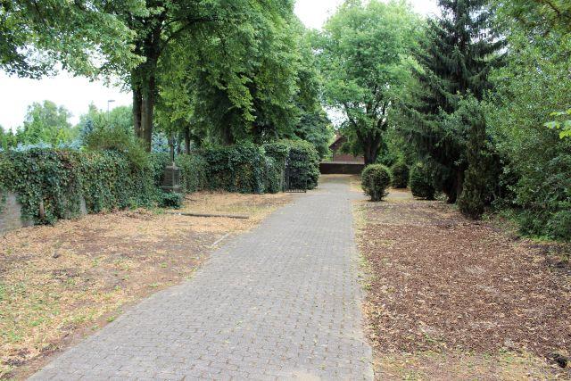 Der Friedhof ist weitgehend ohne Gräber. Auf dem Foto ist noch ein steinernes Kreuz zu sehen, ansonsten braune Erde statt der früheren Gräber.