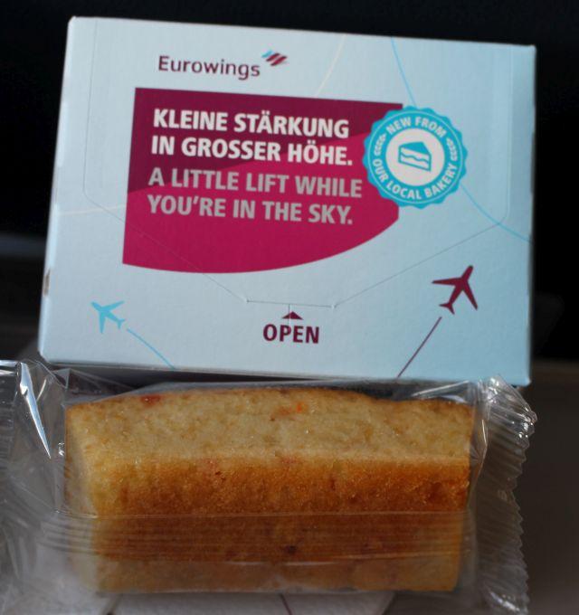 Snack bei Eirowings: Mini-Kuchen und stilles Wasser in einem blau-roten Karton.