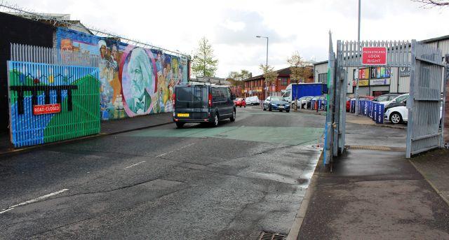 Ein Fahrzeug fährt durch ein Tor der Peace Line in Belfast, das nachts geschlossen wird.