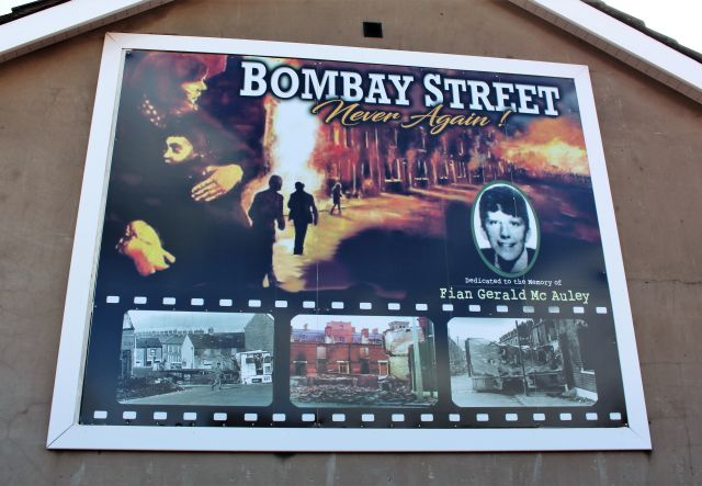 """Ein Wandbild zeigt den Aufruf """"Never again"""" unter dem Straßennamen """"Bombay Street"""" und brennenden Häuser."""