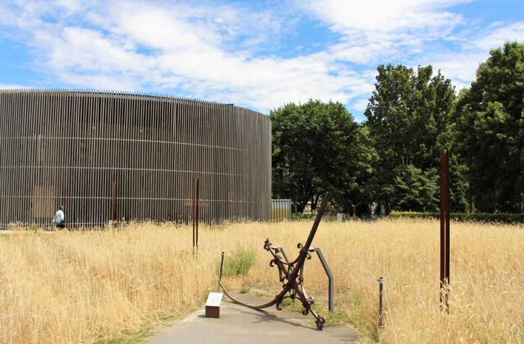 Im Vordergrund das verbogene Turmkreuz der Versöhnungskirche, im Hintergrund nach einem kleinen Weizenfeld die Versöhnungskapelle.