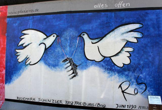 """Zwei weiße Tauben tragen das Brandenburger Tor vor blauem Himmel in die Freiheit. Text: """"Alles ist offen."""""""