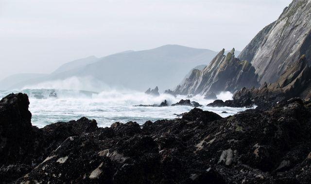 Auflaufende Wellen mit Gischt und schroffe dunkle Klippen.