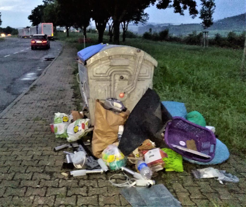 Neben einem vollen silberfarbenen Müllbehälter liegen zahlreiche volle Mülltüten.