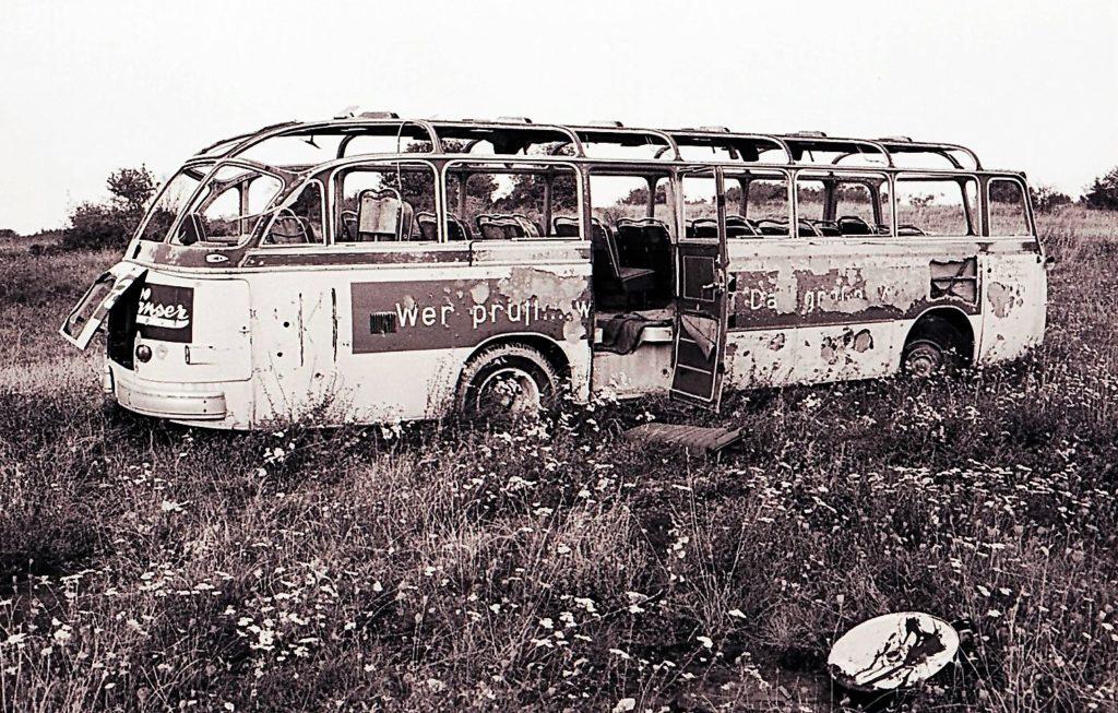 Schwarz-weiß-Foto eines Buswracks auf einer Wiese.