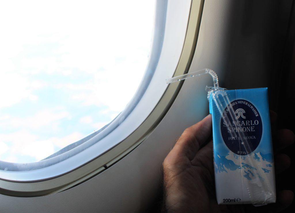 In der Hand des Autors Mineralwasser in Kartonhülle mit einem Trinkhalm aus Kunststoff. Und dies vor dem Fenster im Flugzeug.