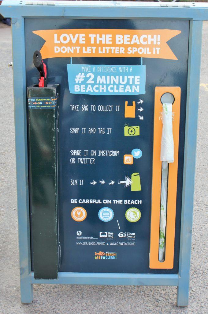 Griffzange und Sammeltüte für Müll werden bei einem Informationsschild bereitgehalten.