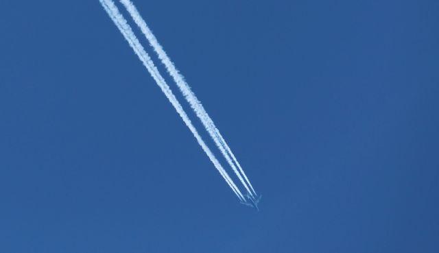 Düsenflugzeug mit Kondensstreifen am blauen Himmel.