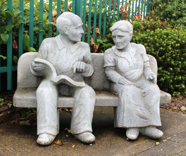 Ein älteres Paar aus grauem Beton sitzt auf einer Bank im Südwesten Irlands.