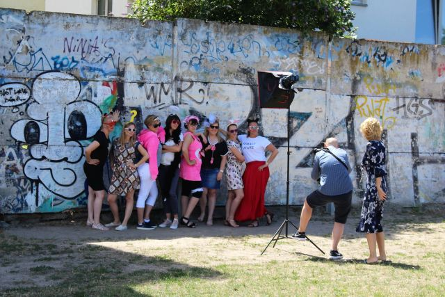 Bunt geleidete Frauen und ein Fotograf mit Ausrüstung an der Berliner Mauer.