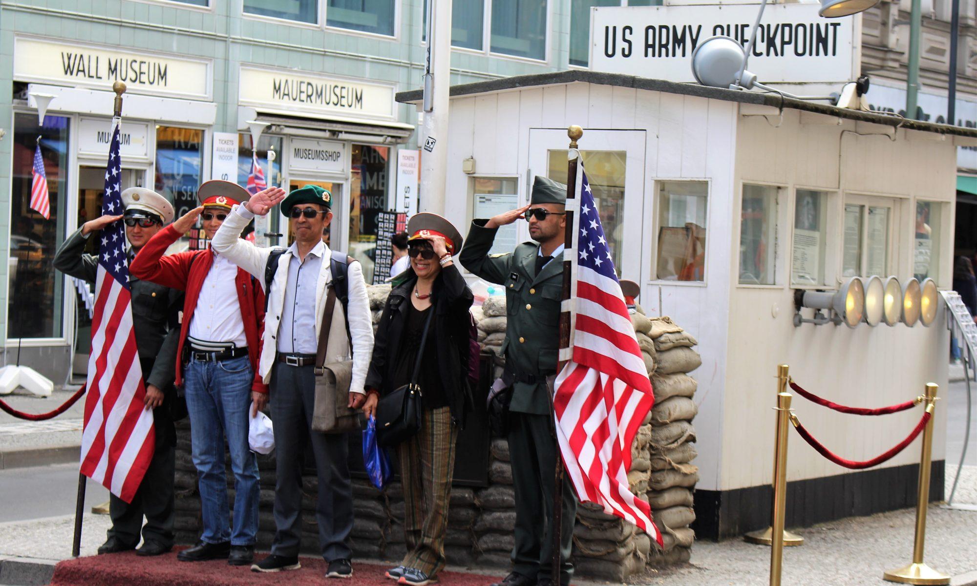 Vier Besucherinnen und Besucher salutieren mit zwei Fake-US-Soldaten am Checkpoint Charlie.
