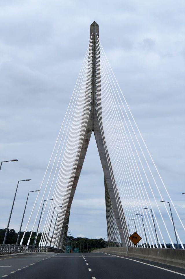 Eine moderne Brücke, deren Fahrbahn an dicken Stahlkonstruktionen aufgehängt ist. Und dies vor einem blau-weißem Himmel.