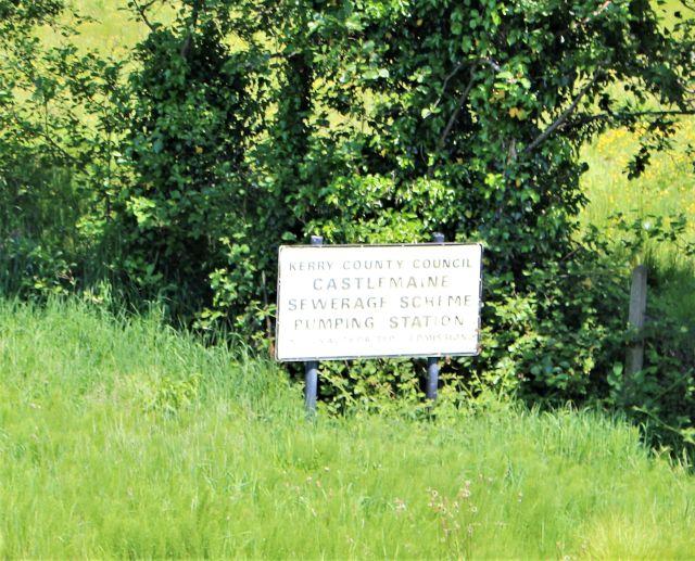 Weißes Schild umgeben von Gras und Bäumen mit dem Hinweis, dass sich hier die Pumpstation für Abwässer befindet.