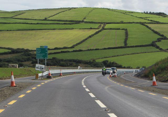 Eine nahezu fertiggestellte Straße mit zwei Fahrbahnen und links und rechts einem Fahrrad- und Fußweg. Erste Fahrzeuge befahren die neue Trasse.
