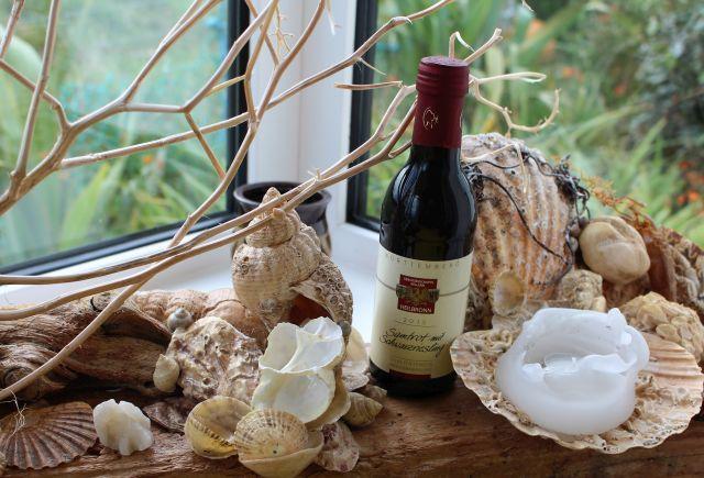 Kleine Flasche mit Rotwein aus der Winzergenossenschaft Flein-Talheim umgeben von Muschelinstallation auf einem Brett vom Strand.