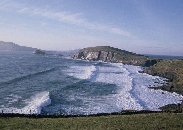 Wellen mit weißer Gischt laufen in Kerry in der Näghe des westlichsten Punkts Europas am Strand und den schroffen Klippen auf.