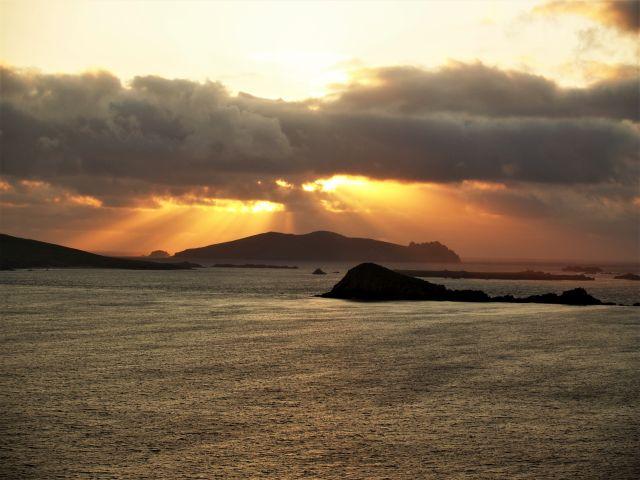 Die Sonne geht golden zwischen den Wolken unter und ihre letzten Strahlen beleuchten den Sleeping Gigant, eine Insel der Blaskets, die einem schlafenden Riesen ähnelt.