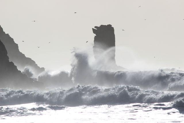 Eine Felssäule umtost von Wellen.