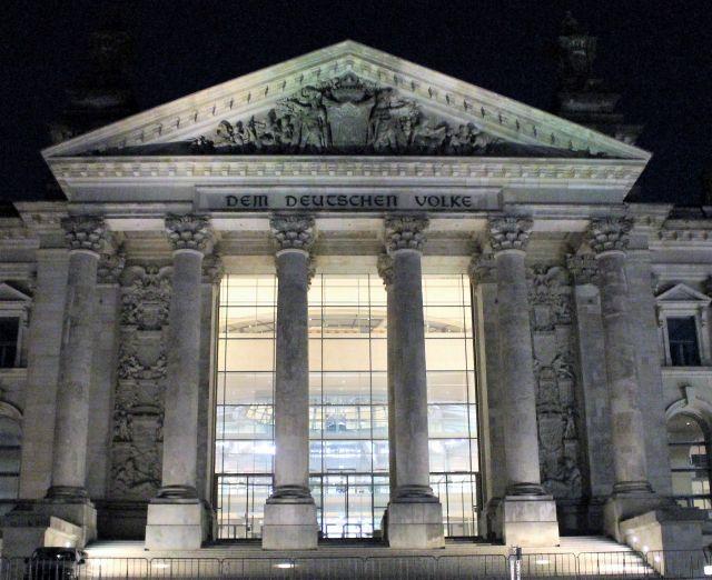 """Der Reuchtag in Berlin von der Frontseite. Der Innenraum ist erleuchtet, die Säulen und das Dach erheben sich gegen den dunklen Himmel. """"Dem deutschen Volke"""" ist zu lesen."""