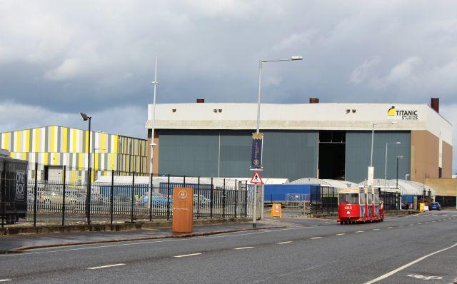 Eine große Halle im Hafengebiet von Belfast mit der Aufschrift 'Titanic Studios'. Im Vordergrund ein kleines rotes Bähnchen für Touristen.