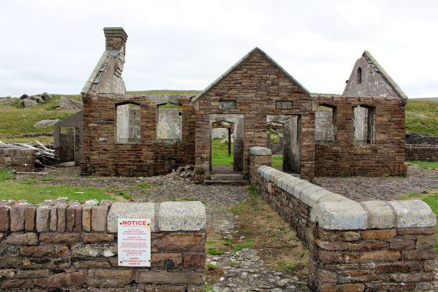 Eine steinerne Mauer führt zu den getrennten Eingängen für mädchen und Jungen. Die Fensterhöhlen sind leer, das Dach fehlt. Die Außenmauern sind aus Feldsteinen mit einem röttlich-braunen Ton.