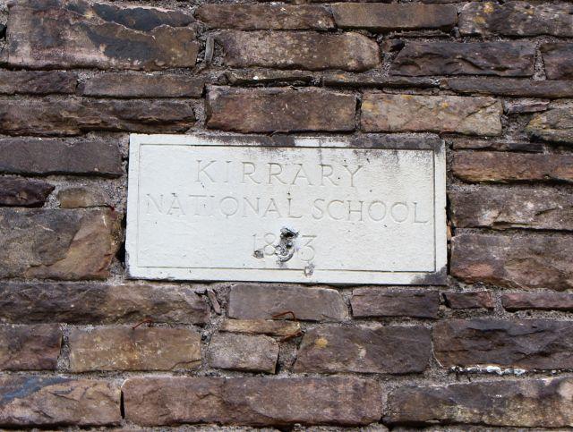 Schild mit dem Text ' Kirray National School 1893' an der steinernen Giebelwand des Schulgebäudes aus 'Ryan's Daughter'.