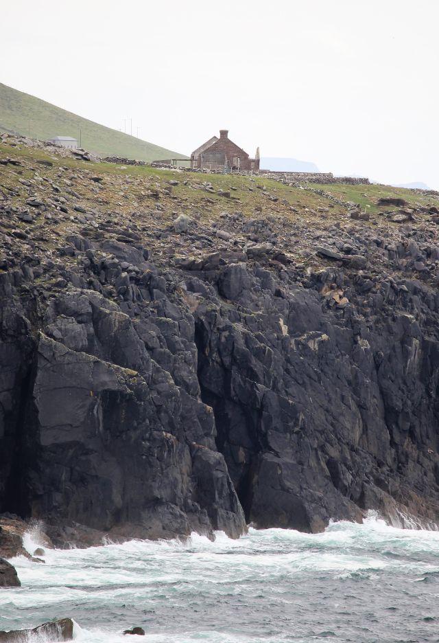 Schroffe dunkle Klippen erheben sich steil aus dem gischtenden Meer und ganz oben die Ruine des Schulhauses.