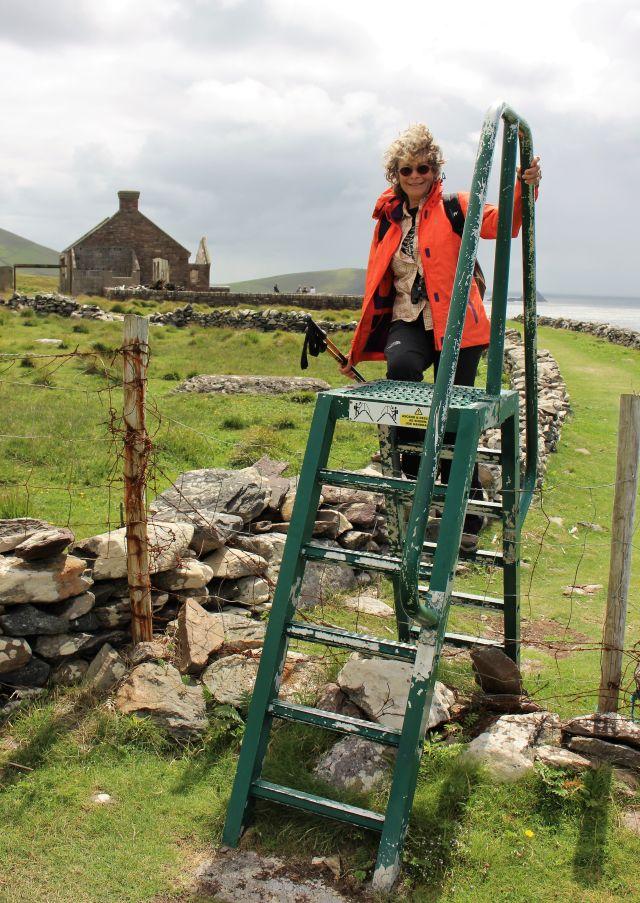 Eine Wandererin mit einer roten Jacke und Wanderstöcken in der Hand klettert über eine Pbersteighilfe aus grünem Metall. Im Hintergrund eine frühere Filmkulisse.