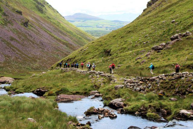 Eine größere Gruppe von Wanderern geht auf einem Pfad talwärts. Neben ihnen fließt ein schmaler Bach. Die Wiesen sind grün, aber die Natur ist insgesamt recht karg.