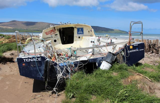 Eine weiße Segeljacht liegt gestrandet auf dem Strand.