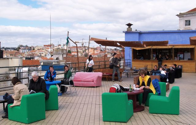 Gäste sitzen auf unterschiedlichen Sesseln und anderen Sitzgelegenheiten. Die Farbe grün dominiert. Im Hintergrund ein Blick auf Lissabon.