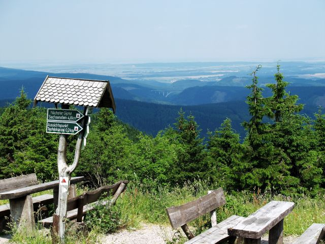 Bänke und Tische laden zum Picknick ein. Im Vordergrund HInweisschilder für die Wanderwege.