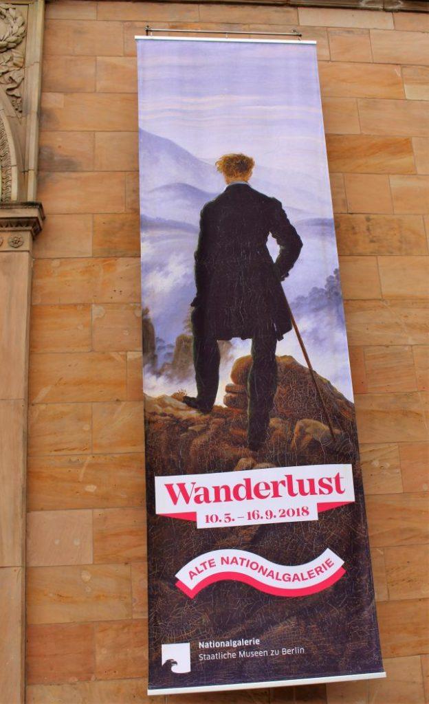 """Werbeplakat der Ausstellung 'Wanderlust' an der Fassade der Alten Nationalgalerie aus rötlichem Stein. Das Bild ist an angelehnt an """"Wanderer über dem Nebelmeer"""" von Caspar David Friedrich."""