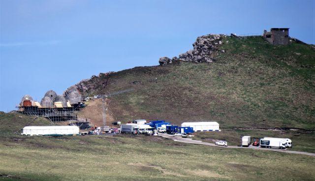 Fahrzeuge und Zelte an einem Berghang, darüber die Fake-Hütten für einen Star Wars Film, die Beehive Huts, den bienenkorbartigen Hütten dienen, in den vor einigen hundert Jahren die Pilger übernachteten.
