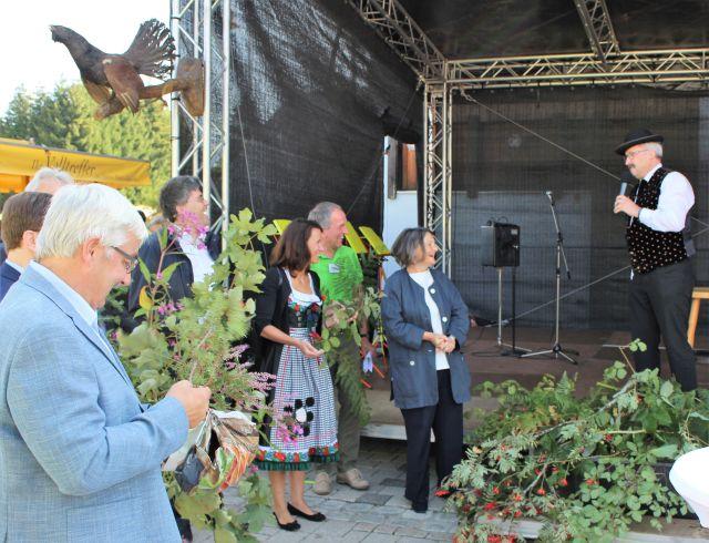 Bärbel Schäfer und weitere Personen mit Zweigen vor einer Bühne.