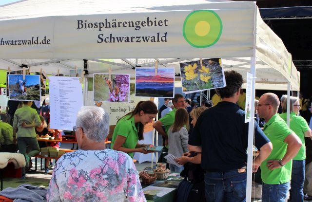 Der Stand trägt den Titel 'Biosphärengebiet Schwarzwald'. Darunter zahlreiche Besucherinnen und Besucher und die Mitarbeiterinnen und Mitarbeiter der Geschäftsstelle in grünen T-Shirts.
