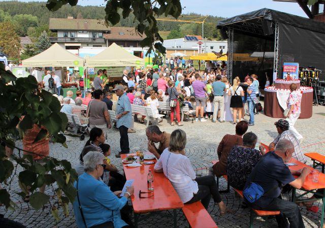 Im Vordergrund Menschen an roten Tischen, weitere Personen auf weißen Bänken und stehend verfolgen eine Tanzvorführung auf der überdachten Bühne.