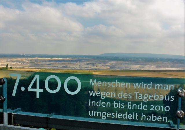Infotafel auf dem Aussichtsturm Indemann mit dem Hinweis, dass für den Tagebau Inden 7400 Menschen umgesiedelt wurden. Im Hintergrund der Tagebau Inden.