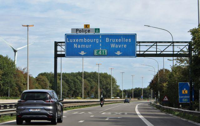 Schilderbrücke über der Autobahn mit den Fahrtrichtungen Luxembourg und Bruxelles in weißer Schrift auf baleum Grund.