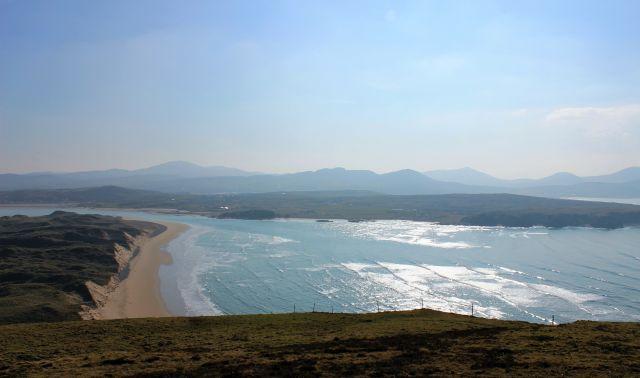 Rechts das sonnebestrahlte blaue Meer, links die grüne Küste mit Klippen und Strand.