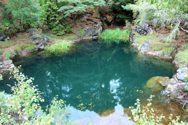 Blau-grün schimmert das Wasser im Blue Hole, einer mit Wasser vollgelaufenen Kupfermine. Im hinteren Bereich umgeben sie Bäume und Gebüsch.