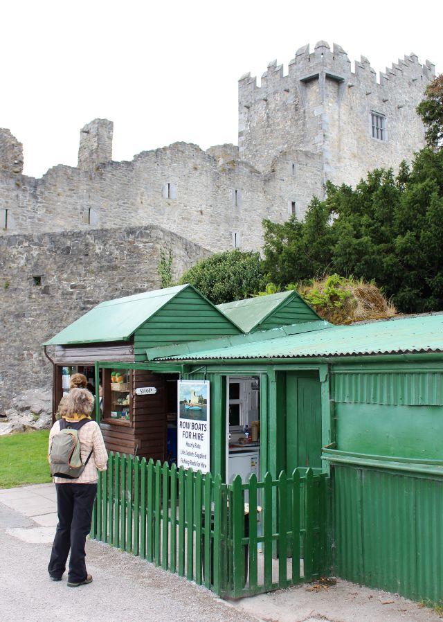 Wanderin vor einem grünen kleinen Coffee Shop. Im Hintergrund erhebt sich Ross Castle aus hellem Gestein.
