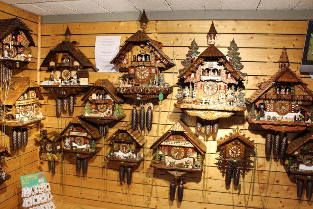Unterschiedliche Kuckucksuhren an einer mit Holz getäfelten Wand in der Erlebniswelt am Mummelsee.