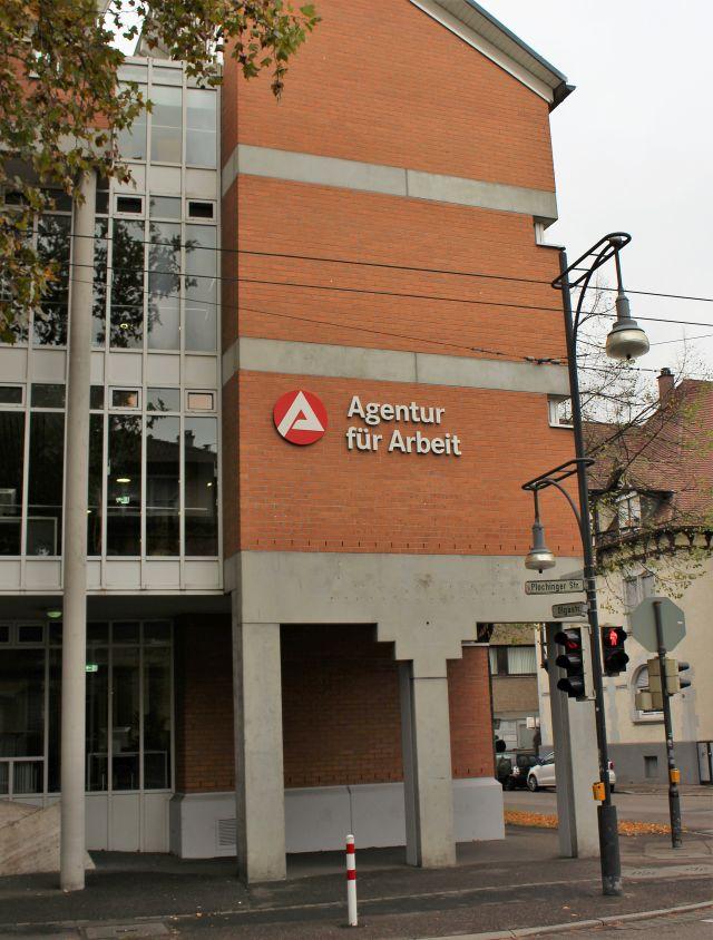 Gebäude aus rotem Backstein und Beton mit der Aufschrift 'Agentur für Arbeit'.