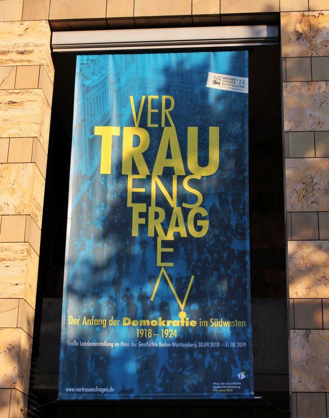 Blaues Banner am Haus der Geschichte. Hellbraune Hausmauer. Auf dem Banner ist 'Vertrauensfragen', der Titel der Ausstellung, zu lesen.