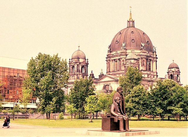 Karl Marx sitzend und FRiedrich Engels neben ihm stehend. Im Hintergrund des Denkmals einige Bäume, der Palast der Republik und der Berliner Dom.