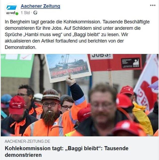 """RWE-Mitarbeiter demonstrieren in roten Arbeitsjacken. Zeitungstitel: """"Kohlekommission tagt: 'Baggi bleibt'. Tausende demonstrieren."""