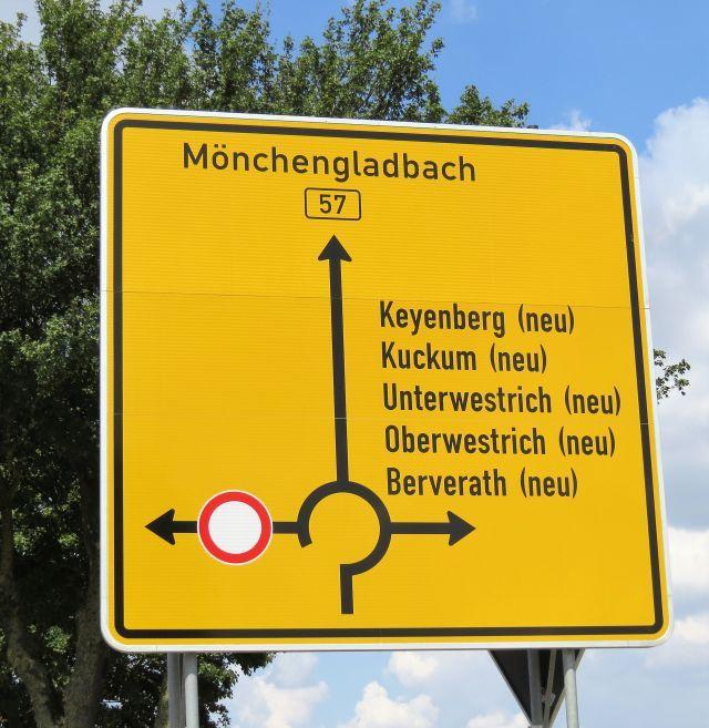 Gelbes Straßenschild mit fünf Ortsnamen und dem Zusatz 'Neu'.